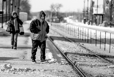 Sarah Nader- snader@shawmedia.com David Badillo of Chicago walks across railroad tracks while waiting for the inbound Metra train to Chicago at the Cary station Tuesday, January 7, 2014. Snow and ice-packed railroad switches along with the number of hours railroad employees can work are causing delays, cancellations and headaches for Metra commuters.
