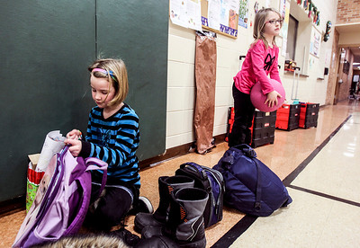 Sarah Nader- snader@shawmedia.com First grader Madi Roth (left), 6, of Crystal Lake packs up her back pack while Hadyn Eimen, 6, of Crystal Lake plays with a ball while at an after-school program at Prairie Grove Elementary School in Crystal Lake Wednesday, January 8, 2014.