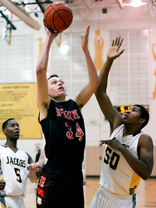 Sarah Nader- snader@shawmedia.com McHenry's Nick Higgin (left) shoots during the third quarter of Wednesday's game against Jacobs in Algonquin January 8, 2014. Jacobs defeated McHenry, 50-53.
