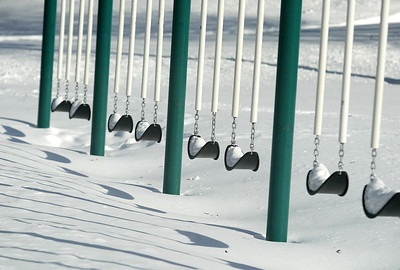 H. Rick Bamman -hbamman@shawmedia.com Snow covered swings sit idle at the Husmann elementary school playground in Crystal Lake. A chance of snow and freezing drizzle after noon is expected on Thursday.
