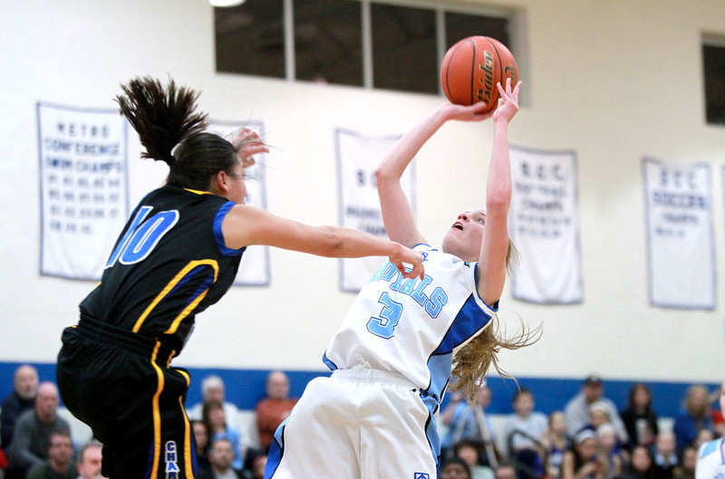 Rosary's Rachel Choice (3) tries to put a shot up past Aurora Central Catholic's Gabi Alfaro during their game at Rosary Thursday night.