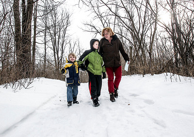 Sarah Nader- snader@shawmedia.com Charlie Peterson (left) 4, Tom Kerver, 12, and their mother, Charlotte Berry of Woodstock look for animal prints during Sunday's winter scavenger hunt hosted by the McHenry County Conservation District at the The Hollows Conservation Area in Cary Sunday, January 12, 2014.