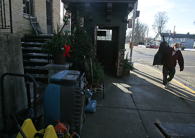 H. Rick Bamman -hbamman@shawmedia.com Michael Novak clears debris from the Riverside Hotel apartment building at 3308 W. Elm St., in McHenry Wednesday, Jan. 8, 2014. The building was declared uninhabitable after a fire started in a three-bedroom apartment Sunday morning.