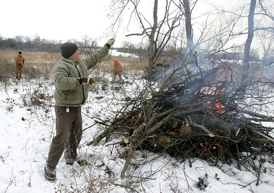 H. Rick Bamman - hbamman@shawmedia.com The Land Conservancy of McHenry County volunteer Randy Schietzelt (cq) (center) of Crystal Lake thows branches onto the fire as Pat Moser (left) of Cary and LCMC stewardship specialist Melissa Hormann (cq) (right) clear brush and trees at the Crowley Sedge Meadow east of Harvard on Wednesday, Jan. 15, 2014.
