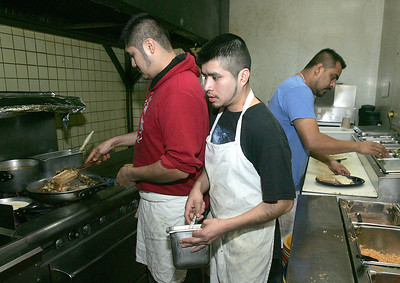 H. Rick Bamman - hbamman@shawmedia.com Pablo's Mexican Restaurant line cooks Carlos Cordoba (left) and Ismael Geron (center) and head chef Noe Garcia prepare lunch orders Thursday, Jan. 16, 2014. Garcia has been with Pablo's for 18 years.