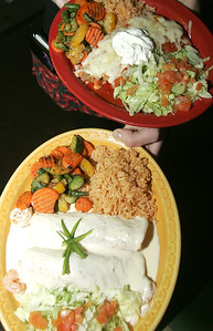 H. Rick Bamman - hbamman@shawmedia.com Pablo's Mexican Restaurant server Sam Quinney (cq) brings out an order of Shrimp Mazatlan Enchiladas (bottom) and Enchiladas Suizas