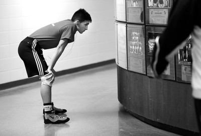 Kyle Grillot - kgrillot@shawmedia.com   Huntley junior Chris Gamboa looks at a picture of the 2010-2011 Crystal Lake South team before the start of the Dual Thursday in Crystal Lake. Huntley lost the dual, 39-34.
