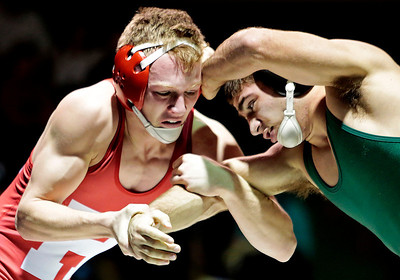Kyle Grillot - kgrillot@shawmedia.com   Huntley junior Brandon Meyer (left) tries to make a move on Crystal Lake's Nick Gil during their match Thursday in Crystal Lake. Huntley lost the dual, 39-34.