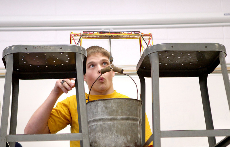 Mooseheart senior Chris Schwartz watches carefully as he adds weights to the bridge he created during the school's 28th Annual Bridge Breaking contest Friday afternoon. Schwartz won the competition with a weight load of 7,300 grams.