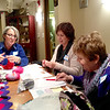 Instructor Gretl Kramer (from left) talks to Noelia Klein of St. Charles and Linda Campise of Geneva on Tuesday during a Zuzu's Petals scarf class at Wool and Co. in St. Charles. Some downtown St. Charles businesses are staying open late this week as part of the Downtown St. Charles Indoor Sidewalk Sale.