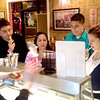 Kimmer's Ice Cream owner Kimberly Elam (left) talks about her specials with Alfredo Garcia, Judy Anderson, Luis Osorio and Melissa Dwinnells on Tuesday during the Downtown St. Charles Indoor Sidewalk Sale.