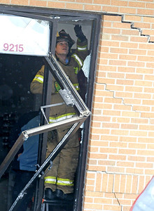 H. Rick Bamman - hbamman@shawmedia.com An Algonquin Lake in the Hills firefighter inspects the interior doorway at the Cosmetology and Nail School at 9215 Trinity Drive in Lake in the Hills Friday afternoon. There were no reported injuries after a Toyota Solara crashed into the building.