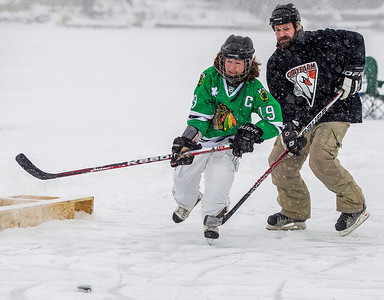 Kyle Grillot - kgrillot@shawmedia.com   Danny Delvecchio of West Dundee (left) and Tim Morgan of Elgin fight for control of the puck during the Pond Hockey Tournament at Woods Creek Lake Saturday in Lake in the Hills. Each of the 14 teams play at least two games on one of the four rinks and the winning team gets to skate the national anthem before the start of a Chicago Wolves game.