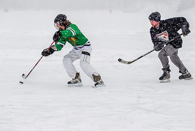 Kyle Grillot - kgrillot@shawmedia.com   Danny Delvecchio of West Dundee (left) and Matt Morgan of Elgin fight for control of the puck during the Pond Hockey Tournament at Woods Creek Lake Saturday in Lake in the Hills. Each of the 14 teams play at least two games on one of the four rinks and the winning team gets to skate the national anthem before the start of a Chicago Wolves game.
