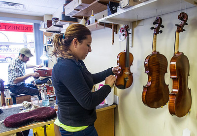 "Kyle Grillot - kgrillot@shawmedia.com   Joel Pautz of Algonquin carves out a new bridge for a cello while Judi Saenz of Crystal Lake cleans violins Monday at Cassandra Strings in Algonquin. According to owner owner Cassandra Thuneman, the cold weather has caused an increase in repair business. ""With the cold, everything is cracking,"" said Thuneman, ""Strings are a living, breathing things. With the furnace on, it expands and if there's not enough moisture, it will crack."" Another round of the record cold temps is expected to hit Tuesday with a high near 6, and wind chill values as low as -23."