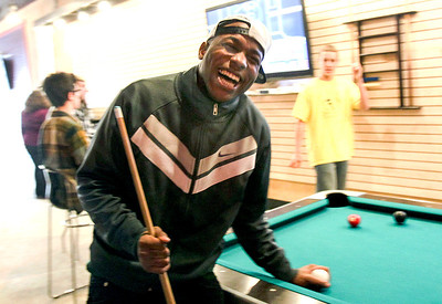 Sarah Nader- snader@shawmedia.com Marquis Wimberly, 17, of  Woodstock laughs after scratching the ball while playing pool with a friend at Revolution Youth Center in Woodstock Tuesday, January 21, 2014. Dunn stops by the center almost everyday after school.