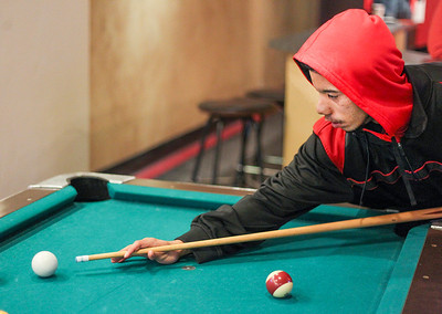 Sarah Nader- snader@shawmedia.com Isaiah Dunn, 18, of Woodstock plays pool with a friend at Revolution Youth Center in Woodstock Tuesday, January 21, 2014. Dunn stops by the center almost everyday after school.