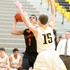 St. Charles East's A.J. Washington (1) tries to get a shot past Metea Valley's Justin Kuehn during their game in Aurora Thursday.
