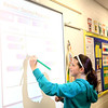 Fifth-grader Kate Stich uses a Smart Board to solve a math problem in Heather Engelhart's classroom at Harrison Street Elementary School in Geneva. The board was donated to the school.