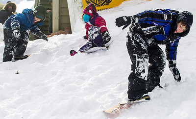 Kyle Grillot - kgrillot@shawmedia.com   Using pieces of cardboard as snowboards, Finnigan O'Hara, 7, (from left) Cayla Allemand, 5, and Nash Bajek, 10, play in the snow during the 109th Norge Ski Jump Tournament held at the Norge Ski Club in Fox River Grove Sunday January 26, 2014.