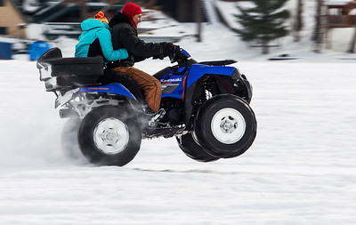 Kyle Grillot - kgrillot@shawmedia.com   The front wheels of his four wheeler become airborne while Alex Warner and his wife Alisa Warner drive on top of the frozen Wonder Lake during the Wonder Lake Sportsman & Conservation Club's 28th Annual Ice Fishing Derby on Wonder Lake Sunday January 26, 2014. The catch and release derby costs $10 per person above the age of 12 and prizes are awarded for the biggest fish of different varieties. All proceeds go towards the conservation of the lake.