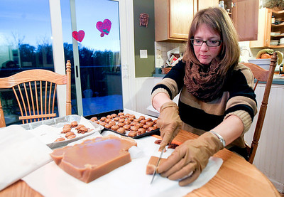 Sarah Nader- snader@shawmedia.com Mary Kay Horney makes chocolate turtles for a church event at her Lake in the Hills home Tuesday, January 28, 2014.  Horney is a member of the Catholic Assistance Mission, which is based in McHenry County and does charitable work in Haiti. She has made a handful of trips to Haiti, and has led trips with local teenagers. To raise money for the trips, she makes and sells chocolate turtle candies.