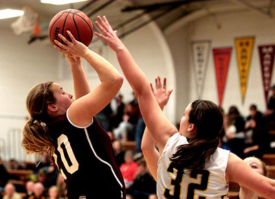 Kyle Grillot - kgrillot@shawmedia.com  Marengo senior Taylor Carlson (20) puts up a shot under pressure from Harvard senior Abby Linhart (32) during the fourth quarter of the girls basketball game Friday in Harvard. Harvard beat Marengo 43-41.