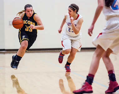 Kyle Grillot - kgrillot@shawmedia.com   Jacobs junior Jessica Powell (33) dribbles towards the net guarded by Marian Central junior Brie Baumert (23) during the second quarter of the girls basketball game Thursday in Woodstock. Jacobs beat Marian Central, 56-48.