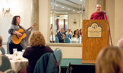 John Konstantaras - For Shaw Media Keryn Moriyah, from McHenry, plays guitar as Bhante Sumana, a monk from the Blue Lotus Buddhist Temple in Woodstock, takes part in an interfaith litany during the FaithBridge Fifth Annual 2015 Martin Luther King Jr. Interfaith Prayer Breakfast at D'Andrea Banquets on Monday January 19, 2015 in Crystal Lake, Ill.