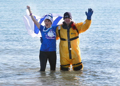 Candace H. Johnson-For Shaw Media Big Cubs fan Diane Cullen, 59, of Grayslake stops to celebrate with Waukegan firefighter Jeff Koch as she runs through Lake Michigan during the 18th Annual Polar Bear Plunge at Waukegan Municipal Beach.