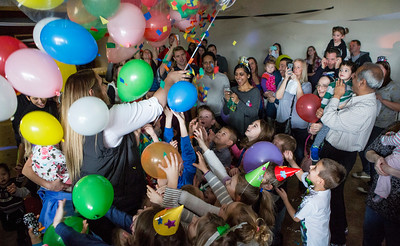 "Mike Greene - For Shaw Media  Children and parents celebrate the ""noon"" year with a balloon drop during a ""Noon Year's Eve Party Saturday, December 31, 2016 at Village Hall in Lake in the Hills. The event included crafting party hats and noise makers, ""snowball toss"" and other games before welcoming in the ""noon"" year with a balloon drop."