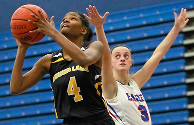 Candace H. Johnson-For Shaw Media Round Lake's Kiara Billups leaps up for a shot against Lakes Shannon Hurlbut in the fourth quarter at Lakes Community High School in Lake Villa.