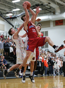 Jack Orndahl (13) from Dundee-Crown is fouled as he battles for a rebound against Gio Calabrese (left) and Brian March (right) from McHenry during the second quarter of their game at McHenry High School on Wednesday, January 11, 2017 in McHenry. The Warriors defeated the Chargers 41-39 in overtime. John Konstantaras photo for the Northwest Herald