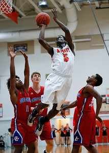 McHenry's Matthew Mohr (5) puts up a shot between Dundee-Crown's Khiry Powell (11) Bradley Stec (23) and Damarion Butler (right) during the first quarter of their game at McHenry High School on Wednesday, January 11, 2017 in McHenry. The Warriors defeated the Chargers 41-39 in overtime. John Konstantaras photo for the Northwest Herald