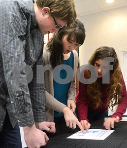 "Nathan Wolfe, (left) from Elmhurst, Abigail Arnold, from Elmhurst, and Barbara Caine, (right) from Hobart, IN, try to figure out a puzzle Jan. 6 at CluedIn Escape Rooms in Glen Ellyn. Participants must decipher puzzles, riddles and other games in order solve a mystery and ""escape"" from a room. Mark Busch - mbusch@shawmedia.com"