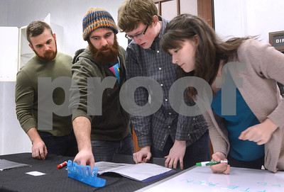 "Matt Strysik, (left to right) from Lisle, Ali Baig, also from Lisle, Nathan Wolfe, of Elmhurst and Abigail Arnold, also from Elmhurst, work through a puzzle Jan. 6 at CluedIn Escape Rooms in Glen Ellyn. Participants must decipher puzzles, riddles and other games in order solve a mystery and ""escape"" from a room. Mark Busch - mbusch@shawmedia.com"