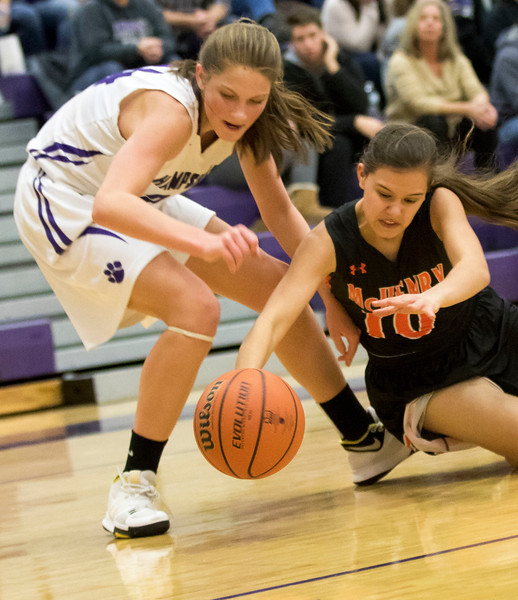 Sarah Nader - snader@shawmedia.com Hampshire's Kelby Bannerman (left) and  McHenry's Ashley Wachter dive for the ball during the first quarter at Friday's game in Hampshire Jan. 5, 2018. McHenry won, 53-48.