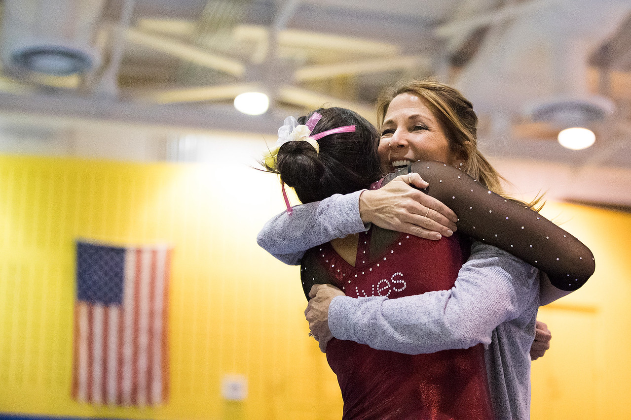 Whitney Rupp - for Shaw Media Prairie Ridge gymnastics assistant coach Lisa Rumford hugs Maddy Kim after Kim's beam performance at the Lake Forest Invitational Jan. 6.