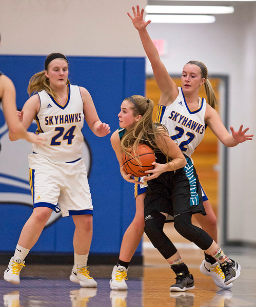 Hanna Seils (11) from Woodstock North works her way past Johnsburg defenders Mackenzie Straulin (24) and Heather Arden (22) during the second quarter of their game at Johnsburg High School on Monday January 22, 2018 in Johnsburg, Illinois. John Konstantaras photo for Shaw Media