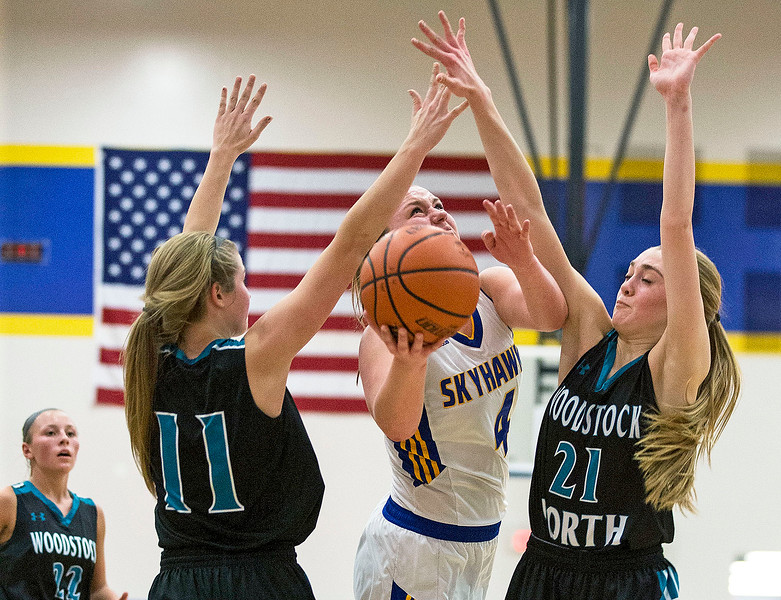 Megan Madsen (4) from Johnsburg puts up a shot between Hanna Seils (11) and Kaitlyn Ford (21) from Woodstock North during the second quarter of their game at Johnsburg High School on Monday January 22, 2018 in Johnsburg, Illinois. John Konstantaras photo for Shaw Media