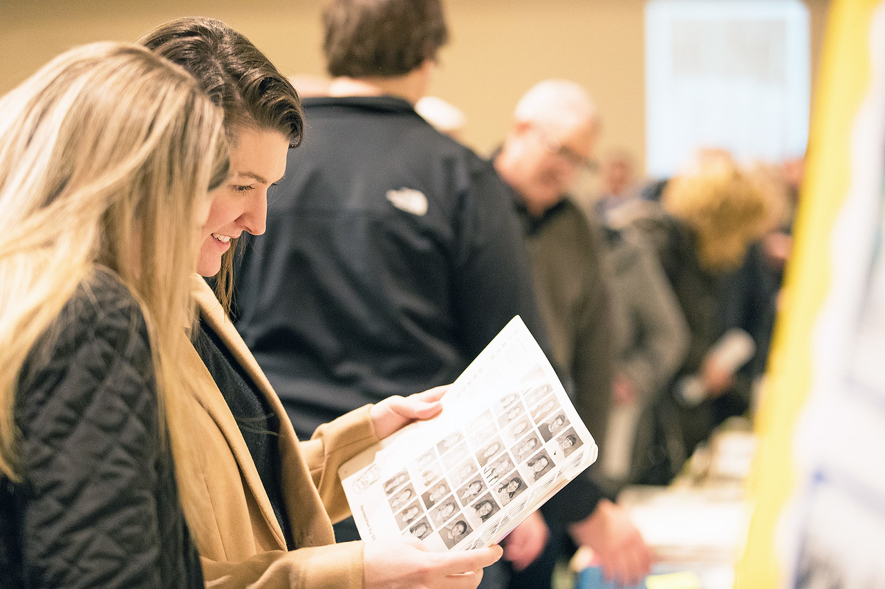 Whitney Rupp for Shaw Media Katie Cooper, Madison, Wisc., pages through a yearbook at the celebration of St. Thomas School's 90th anniversary in Crystal Lake Jan. 27.