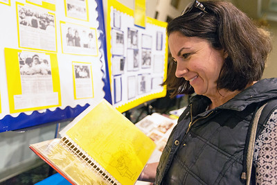 Whitney Rupp for Shaw Media Theresa Dalton, St. Thomas Class of 1989, enjoys photographs on display at the 90th anniversary celebration of St. Thomas School Jan. 27.