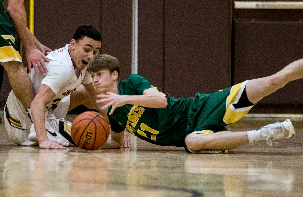 Sarah Nader - snader@shawmedia.com Jacobs' Nikolas Balkcom (left) and Crystal Lake South's Matthew Reall drive for a lose ball during the first quarter Wednesday at Jacobs' Hinkle Holiday Classic Dec. 27, 2017. Jacobs won, 54-40.