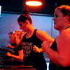 Kelly Cone (right) of Sugar Grove and Krista Parrino of West Chicago (left) run on treadmills during a class at Orangetheory Fitness in St. Charles. Fitness research shows that when people work out as buddies or in groups, they tend to keep each other honest in sticking to their regimens.