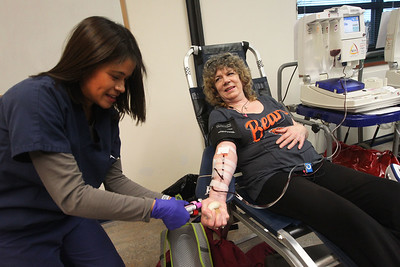 "Candace H. Johnson-For Shaw Media Aurora Lopez, of Waukegan, a phlebotomist, takes O Negative blood from Beverly Menta, of Grayslake while she is attached to a Alyx machine during the Vitalant Blood Drive at the Grayslake Area Public Library.O Negative blood cells are ""universal,"" meaning they can be transfused into almost any patient in need. (12/27/18)"
