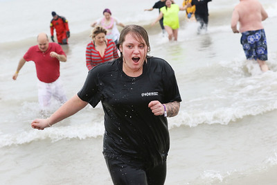 Candace H. Johnson-For Shaw Media Blair Gartley, of Waukegan feels the cold as she comes out of Lake Michigan during the 20th Annual Waukegan Polar Bear Plunge at Waukegan Municipal Beach. The event was hosted by the Waukegan Park District and the City of Waukegan. Proceeds from the event will go to the Special Recreation Services of Northern Lake County. (1/1/19)