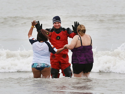 Candace H. Johnson-For Shaw Media Magda Prado and Pam Zanco, both of Waukegan give a high-five to Dustin Rynders, a Waukegan firefighter, as they make their way through Lake Michigan during the 20th Annual Waukegan Polar Bear Plunge at Waukegan Municipal Beach. The event was hosted by the Waukegan Park District and the City of Waukegan. Proceeds from the event will go to the Special Recreation Services of Northern Lake County. (1/1/19)