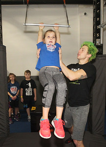 Candace H. Johnson-For Shaw Media Kara Dietz, 8, of Barrington gets some help from Pro Ninja Jamie Rahn as she swings on a trapeze bar during Pro-Camp V at Ultimate Ninjas in Libertyville. (1/5/19)