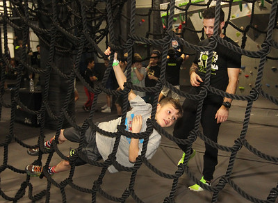 Candace H. Johnson-For Shaw Media Luke Farrell, 6, of Libertyville gets some encouragement from Pro Ninja Brian Redard, of Naperville as he conquers a climbing obstacle course during Pro-Camp V at Ultimate Ninjas in Libertyville. (1/5/19)