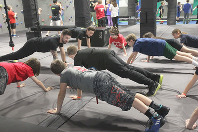 Candace H. Johnson-For Shaw Media Pro Ninjas Brian Redard and Tori Clement, both of Naperville do push ups with a group of kids as they warm up before being challenged on obstacle courses during Pro-Camp V at Ultimate Ninjas in Libertyville. (1/5/19)